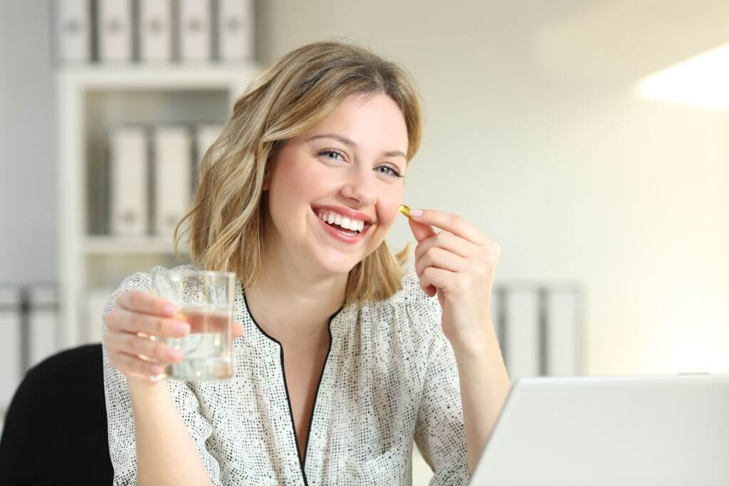 Smiley face women take a vitamin supplement